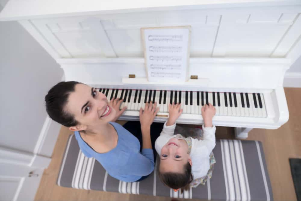 mother playing piano with child